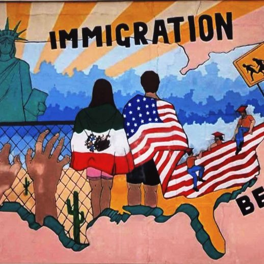 """A mural that showing two figures in American and Mexican flags looking at a chain link fence with the Statue of Liberty beyond. The words """"immigration is beautiful"""" are to the side"""