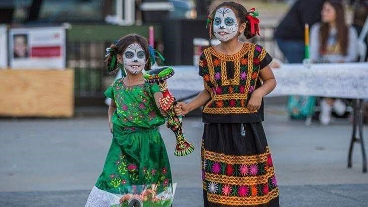 Two girls in Day of the Dead outfits and makeup